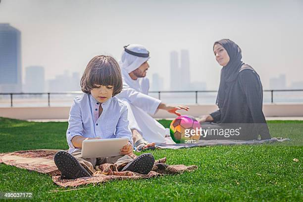 Little arab boy using digital tablet in the park