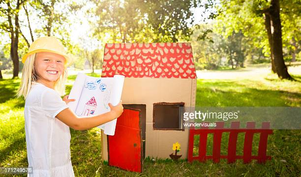 Little architect in front of playhouse