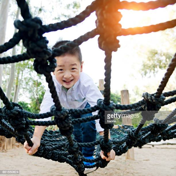 Little asian boy climbing rope frame