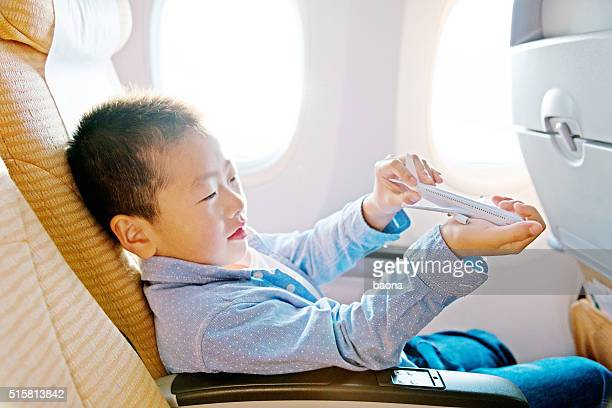 Little asian boy playing a toy plane