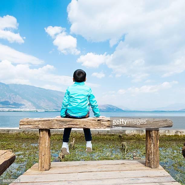 小さなアジアの少年に座っている湖の桟橋