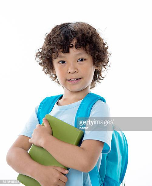 Little asian boy with a book against white background