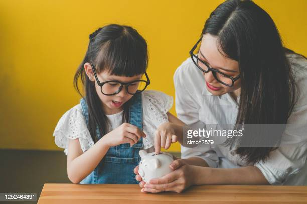little asian cute girl putting money to piggy bank with her mother - spelling stock pictures, royalty-free photos & images