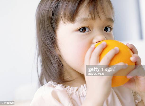 Little Asian girl biting into an orange