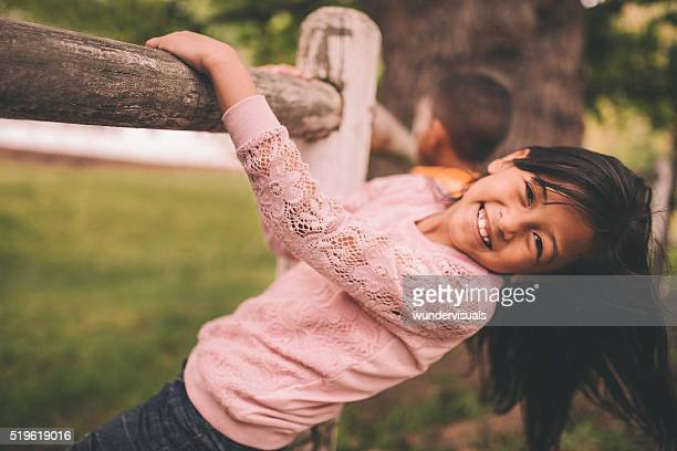 Little asian girl hanging on a wooden fence in park