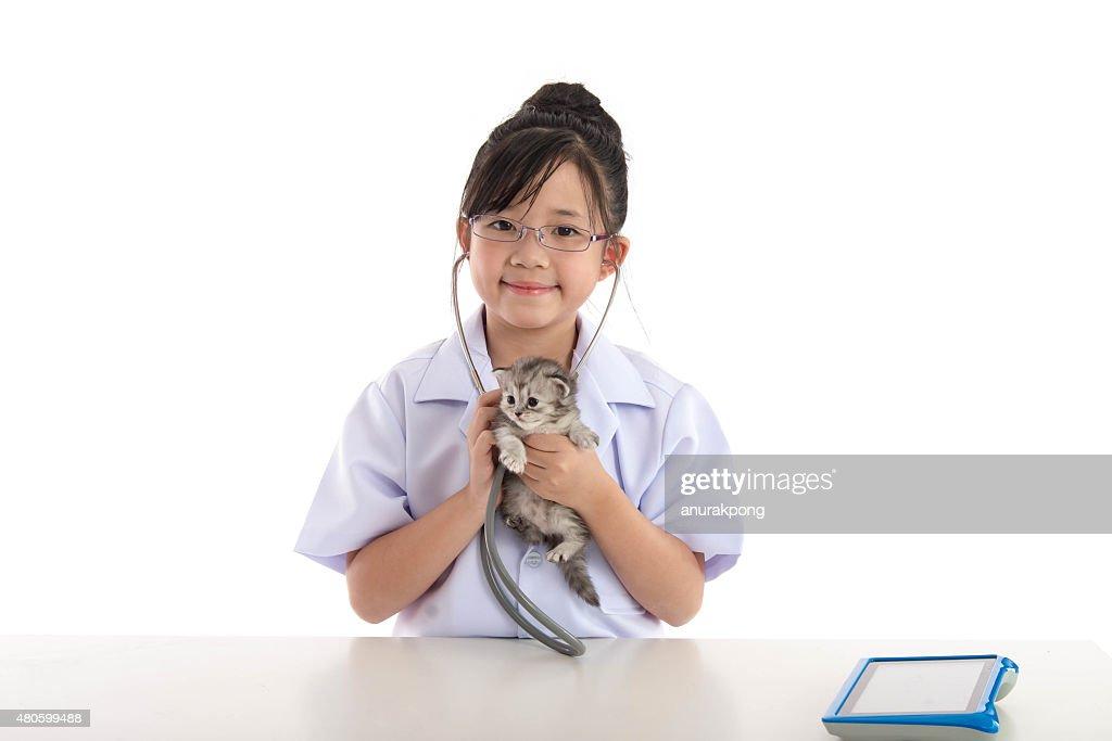 Little asian girl playing veterinarian with kitten : Stock Photo