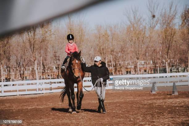 aziatische meisje nemen een les rijden - paardrijden stockfoto's en -beelden