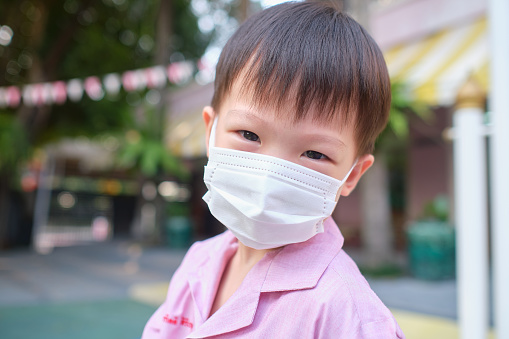 Little Asian toddler boy child wearing protective medical mask at school, Concept of coronavirus quarantines and Air pollution pm2.5 concept 1203982670