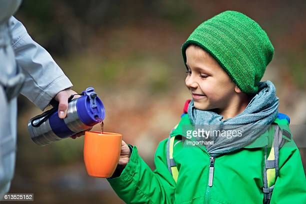 Little autumn hiker drinking hot tea