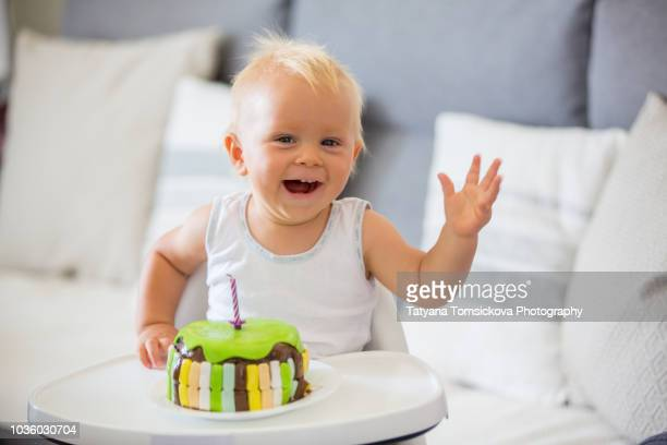 little baby boy, eating cake for his first birthday in high chair at home - anniversaire humour photos et images de collection