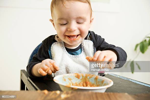 Little baby boy having fun messing with food