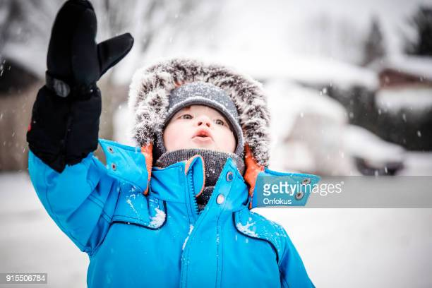 Little Baby Boy in Blue Winter Clothes Having Fun With Snow