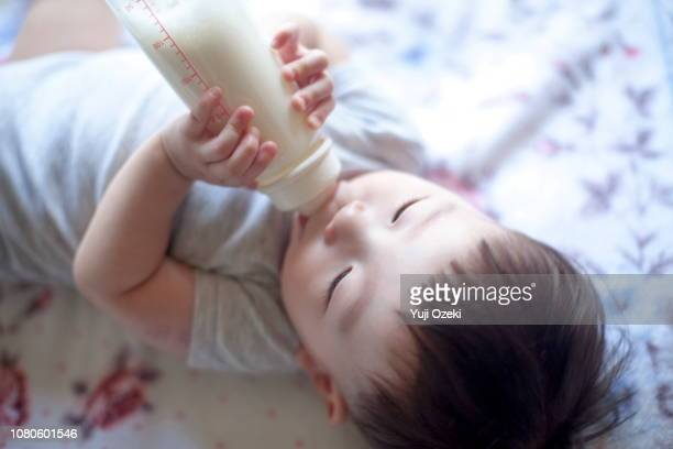 little baby boy lying down and drinking milk he owned - japanese breastfeeding stock pictures, royalty-free photos & images