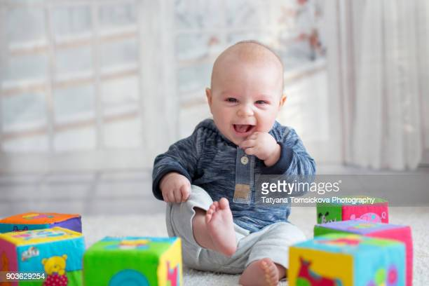 Little baby boy, sitting at home in living room, playing with colorful blocks and toys, smiling at camera