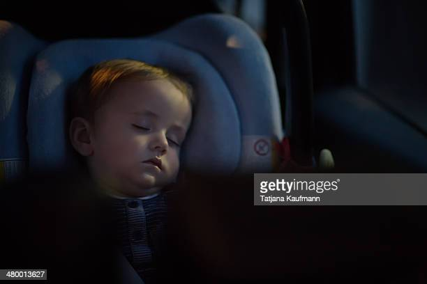 Little Baby Boy soundly sleeping in Car Seat