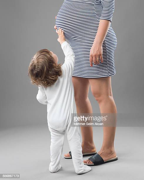 little baby boy touching pregnant mother's belly - striped dress stock photos and pictures