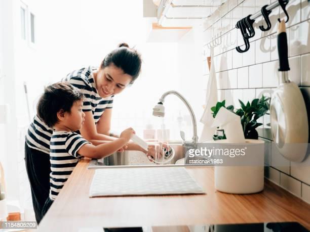 小さな男の子は彼の母親と一緒にきれいな料理を拭きます。 - 洗う ストックフォトと画像