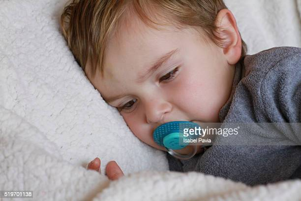 Little baby boy with pacifier on bed