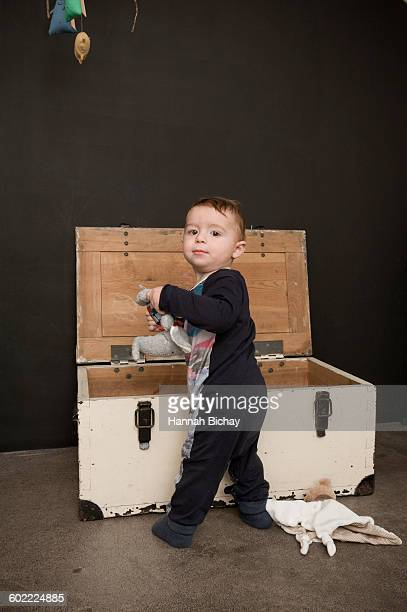 little baby boy with toys in a wooden box