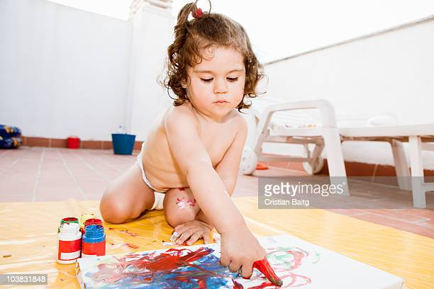Little baby girl painting with her fingers