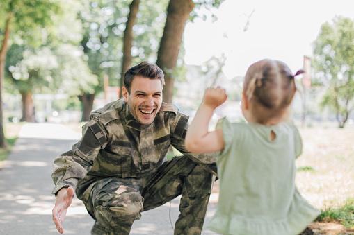 Little baby girl running towards soldier 975774500