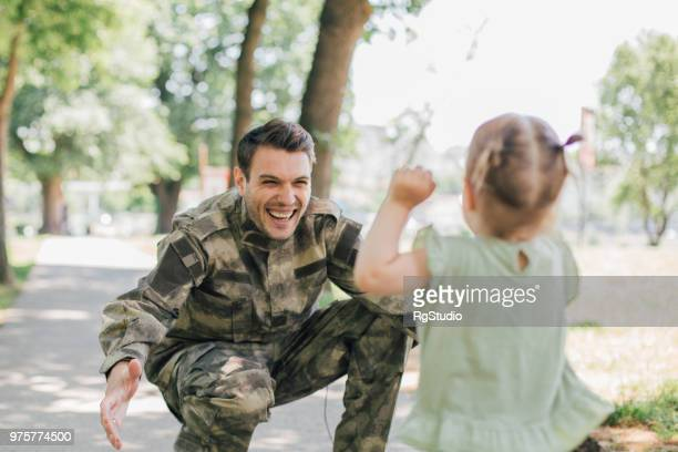 little baby girl running towards soldier - happy memorial day stock pictures, royalty-free photos & images