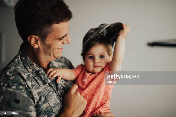 little baby girl taking hat of her head while daddy holding her in his arms - infantería stock pictures, royalty-free photos & images
