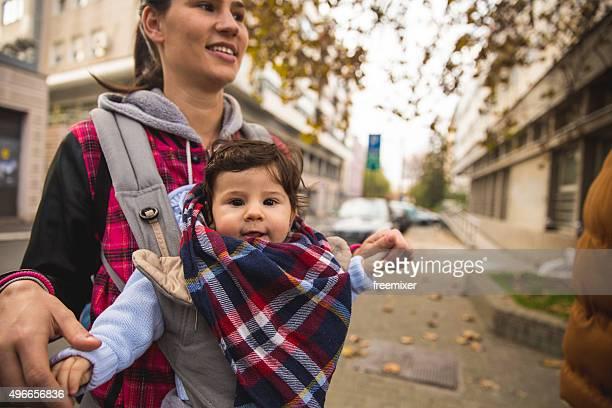 Little baby in baby carrier in city walk