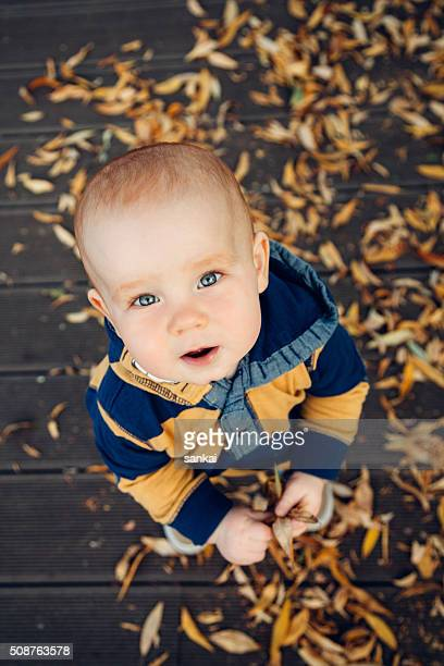 Little baby playing with autumn leaves on a wooden floor