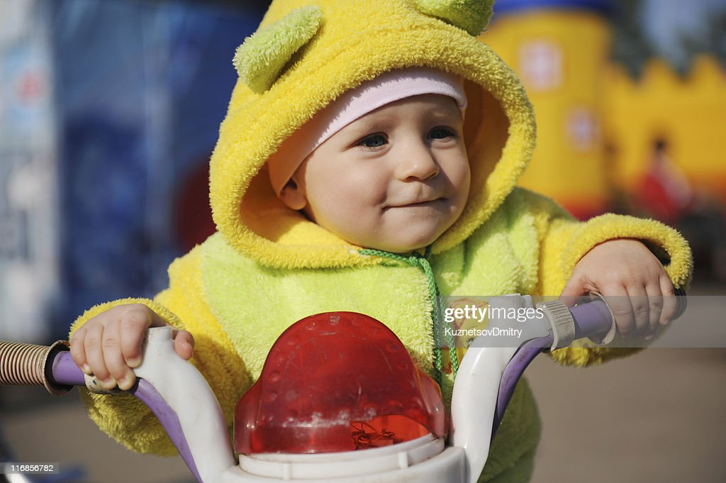 Little baby plays with the bike on street : Stock Photo