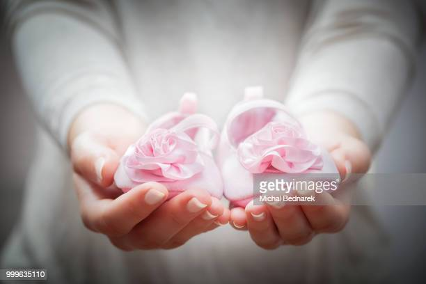 Little baby shoes in woman's hands. Concepts of waiting for a child, charity, mother etc.