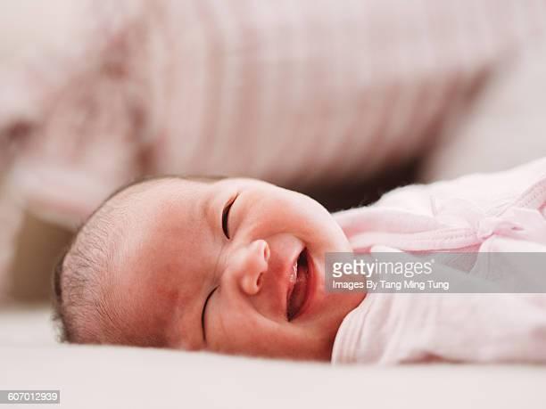 Little baby smiling joyfully on bed