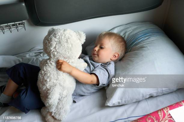 little baby with blue eyes lies in bed and hugging his favorite toy - ukraine stock pictures, royalty-free photos & images