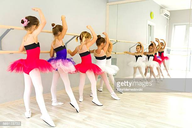 little ballerinas in tutu using barre and practicing postures. - barre class stock photos and pictures