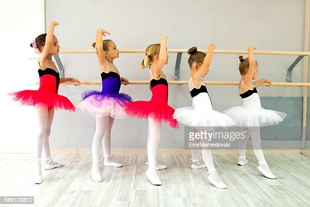 Little ballerinas in tutu using barre and practicing postures.