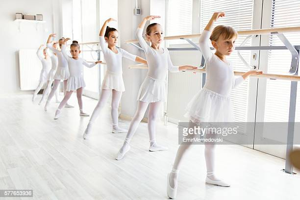Little ballerinas using barre while practicing in dance studio.