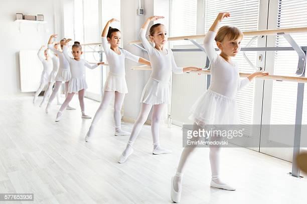 pequenas bailarinas usando barre enquanto praticam em estúdio de dança. - bailarina - fotografias e filmes do acervo
