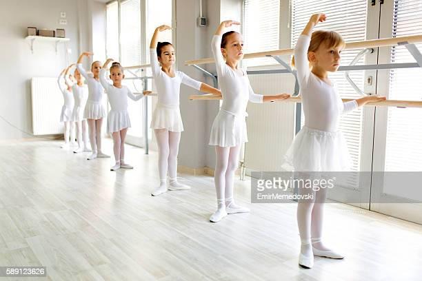 little ballerinas using barre while practicing in dance studio. - ballettstudio stock-fotos und bilder