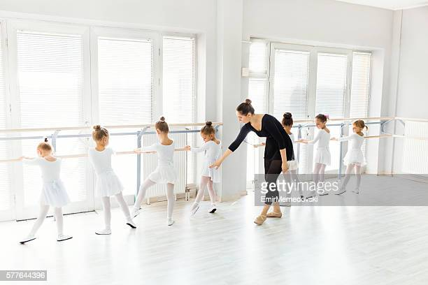 Little ballerinas with personal ballet teacher in dance studio.
