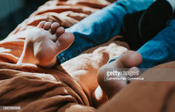 little bare feet on a soft bed, focus on soles and toes - human leg stock pictures, royalty-free photos & images