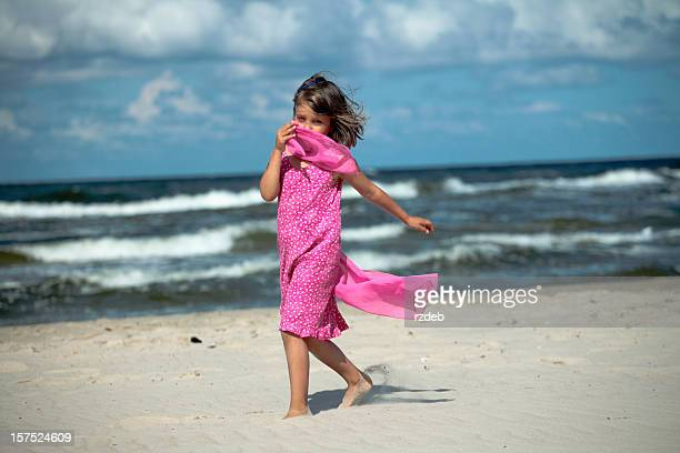 Little Beautiful Girl in Pink Dress Running on the Beach