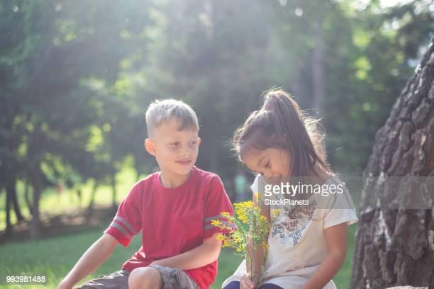 Niña belleza consiguió una flor de chico lindo en el bosque