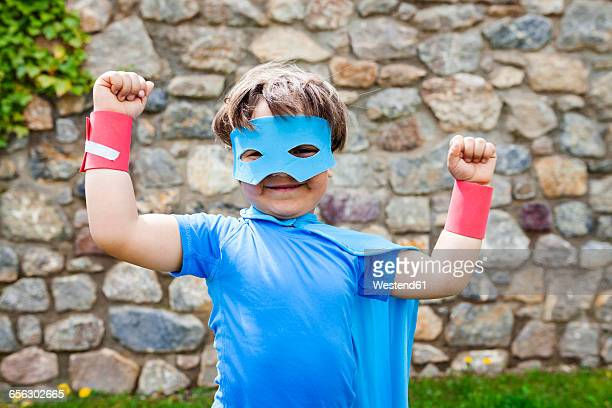 Little big hero with a mask against a stone wall