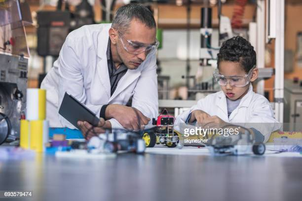 Little black boy and teacher making a robot for school science project.