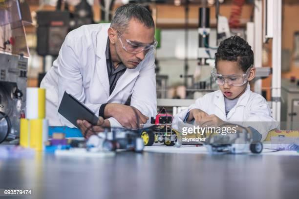 Kleinen schwarzen Jungen und Lehrer machen einen Roboter für Wissenschaft Schulprojekt.