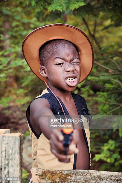 """little black boy playing cowboy with a toy gun. - """"martine doucet"""" or martinedoucet stock pictures, royalty-free photos & images"""