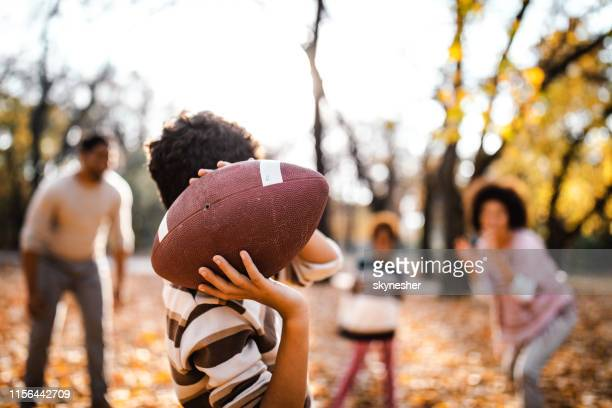 little black boy playing rugby with his family at the park. - activity stock pictures, royalty-free photos & images