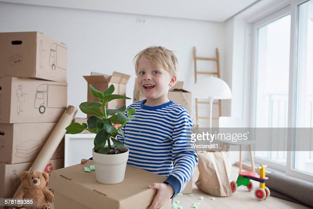 Little blond boy helping with cardboard boxes