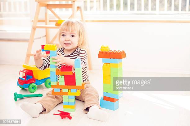 Little blond child playing with colorful plastic blocks