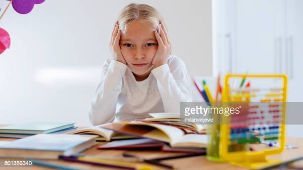 Little blond girl bored with her homework